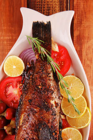 main course: whole fryed sunfish on wooden table with lemons and peppers Stock Photo - 12529433