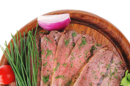 grilled beef slice on wooden plate over white photo