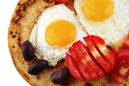 uk cuisine: fried eggs on pancake over white with vegetables
