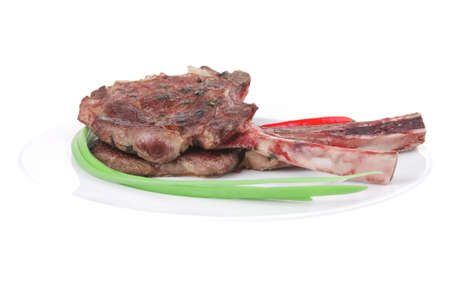 served main course: grilled pork ribs served with green chives and raw red chili peppers on white dish isolated over white background Stock Photo - 12694235