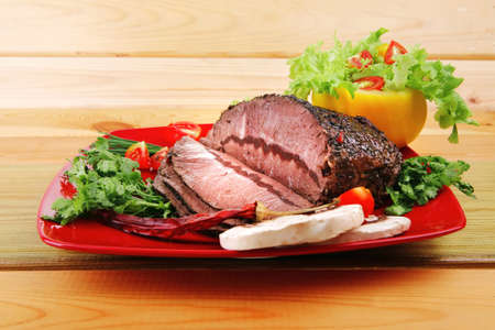 hot beef on red plate over wood table   photo