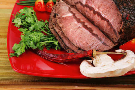 beef slice on red plate and vegetables on wood Stock Photo - 12699499