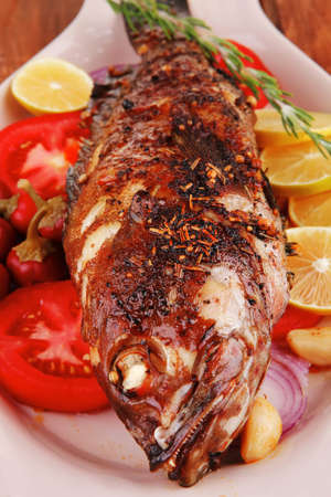 whole fried bass on plate, served with lemons and tomatoes Stock Photo - 12707253