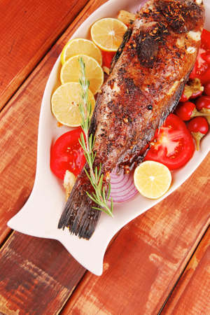 main course: whole fryed sunfish on wooden table with lemons and peppers Stock Photo - 12707669