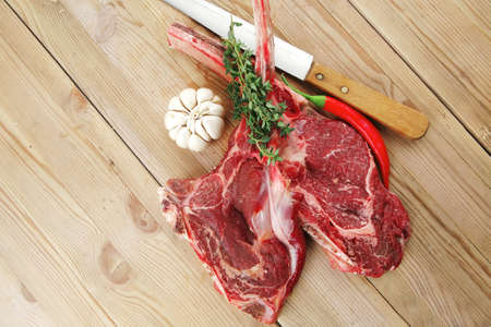 fresh raw meat : fresh red beef ribs with thyme , garlic and red chili pepper over wooden table photo