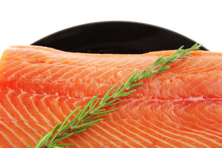 fresh raw salmon fillet on black over white and rosemary photo