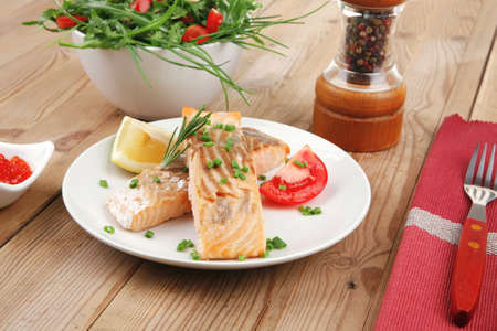 healthy fish cuisine : grilled pink salmon steaks with red caviar in white bowl , lemon and vegetable salad on white dish with cutlery and pepper grinder over wooden table photo