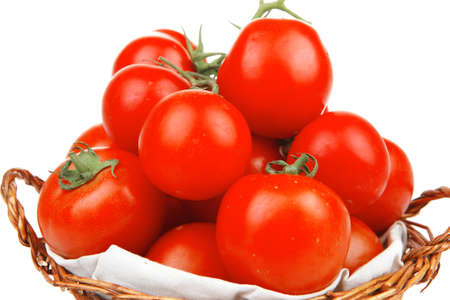 raw fresh tomatoes in wicker basket on green branch isolated on white background photo