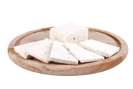 queso de cabra: rebanadas de queso blanco de cabra en la placa de madera