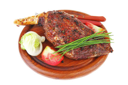 meat on wooden plate : roast shoulder on wood with tomatoes chives and green lettuce isolated on white background photo