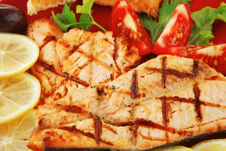 grilled salmon and lemon on red plate photo