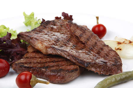 meat food : two grilled steak with chili and red peppers , green lettuce salad , on dish isolated over white background Stock Photo - 12714630