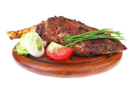 stell: meat over wood: grilled shoulder on plate with tomatoes green lettuce and cutlery isolated on white background