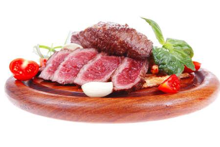 carne asada sobre patata: carne fresca, carne a la parrilla en la placa de madera con pimiento y tomate aisladas sobre fondo blanco Foto de archivo