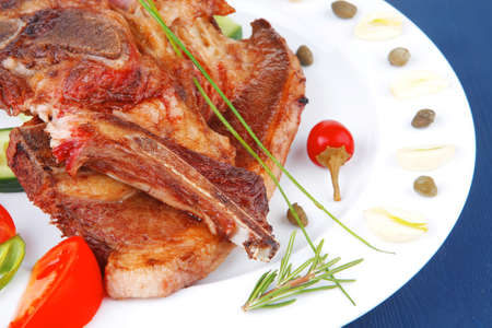 fresh roasted beef meat bone steak on ceramic dish with red hot pepper and tomatoes over blue wood table Stock Photo - 12767313