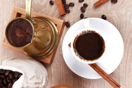 sweet hot drink : black arabic coffee in small white cup with mortar and pestle , bag full beans, copper old style cezve , decorated with cinnamon sticks and anise stars photo