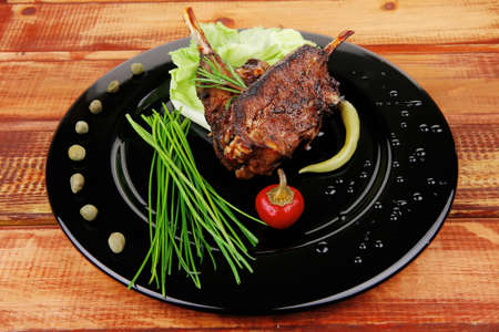 image of served meat: spiced barbecued ribs on black plate with peppers chives and capers photo