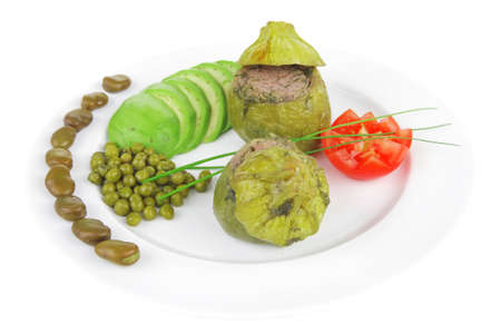 meat meal: round zucchini filled mince meat over white dish served with vegetables photo