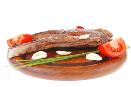 fresh hot roasted lamb meat fillet ready on red wooden plate with tomatoes, green pepper , and garlic isolated over white background Stock Photo - 12767195