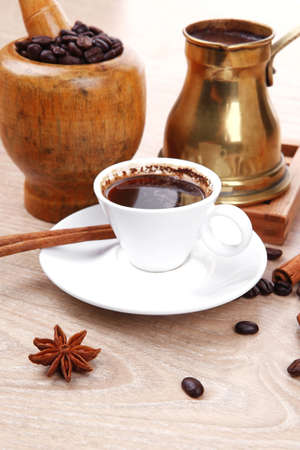 cezve: sweet hot drink : black turkish coffee in small white mug with mortar and pestle , coffee beans in white bag , copper old style cezve full hot coffee, decorated with cinnamon sticks and anise stars Stock Photo