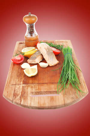 savory fish portion : grilled norwegian salmon fillet with green chinese onion, red cherry tomatoes , allspice pepper in grinder, rosemary twigs and lemon slice on wooden board isolated over white background photo