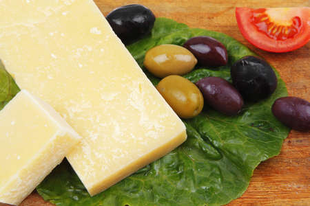 solid parmesan on wooden platter with olives and tomato isolated over white background Stock Photo - 12766795