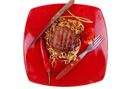 grilled beef fillet pieces on noodles , red hot chili pepper and tomato on red plate isolated over white background photo