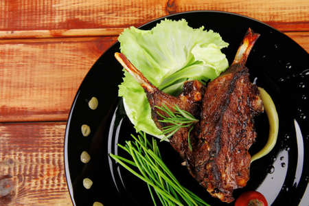 sawory on black: grilled ribs on plate over wooden table photo