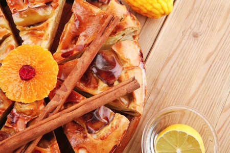 baked food: apple pie cuts on wooden plate served with fresh lemon, mandarin, and cinnamon sticks on table photo