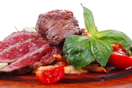 meat food : grill beef on potato chips with fresh tomato and hot green peppers on wood plate isolated on white background photo