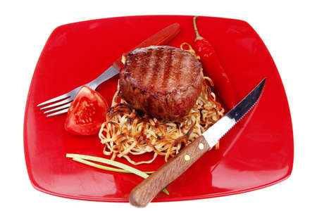 grilled beef fillet medallions on noodles and red hot chili pepper on red plate isolated over white background photo