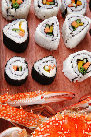 Roll with Cucumber , Cream Cheese with raw Tuna and Salmon inside. on wooden plate with live crab  . Isolated over white background . Japanese traditional Cuisine Stock Photo - 13028583