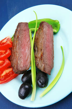 meat savory : grilled beef fillet mignon served on blue plate over blue wooden table with chili pepper and tomatoes photo