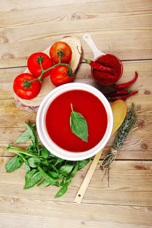 diet food : fresh cold tomato soup with basil thyme and dry pepper in big bowl on wood table photo
