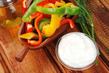 peppers sliced for salad on wooden table photo