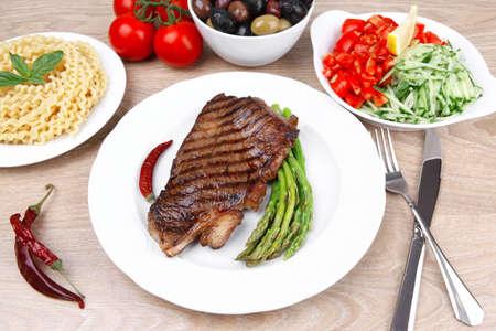mesa de la carne: asado de filete de res medio crudo y pasta con esp�rragos tomates y varios tipos de aceitunas, servido en un plato blanco sobre madera clara Foto de archivo - 13147128