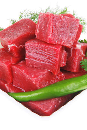 raw fresh beef meat slices in a white bowls with dill and green hot peppers isolated over white backkground