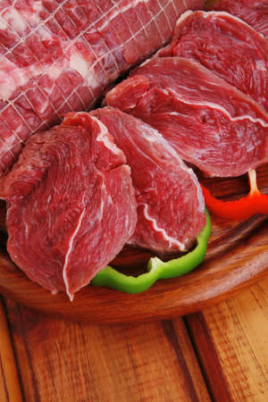 fresh raw red meat on wooden table photo