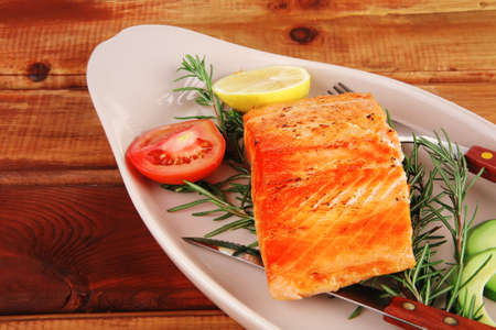healthy food: hot baked salmon piece served over glass plate on wood Stock Photo - 13172672