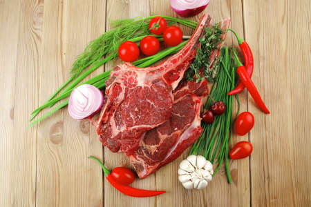 boned: raw meat : boned fresh lamb ribs served with thyme , red chili pepper , cherry tomato , and green onion over wooden table