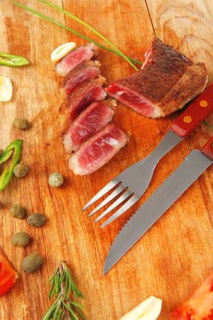 fresh roasted beef meat steak sliced on wooden board with cutlery isolated  over white background photo