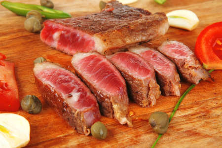 fresh grilled beef meat fillet sliced on wooden board with cutlery isolated  over white background photo
