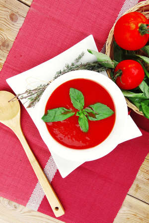 cold fresh diet tomato soup with basil thyme and dry pepper in big bowl over red mat on wood table ready to eat photo