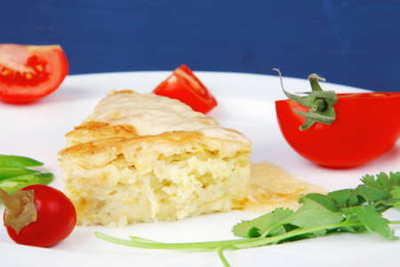 food : cheese casserole piece over white plate served with peppers and tomatoes on blue table Stock Photo - 13423067