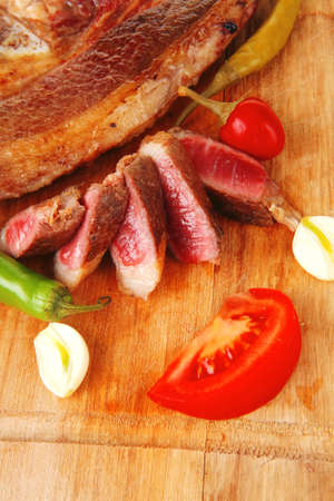 fresh roasted beef meat steak sliced on wooden board with red hot pepper cutlery isolated  over white background photo