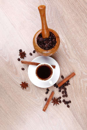 sweet hot drink : black arabic coffee in small white cup with mortar and pestle , beans spilled over wooden table , decorated with cinnamon sticks and anise stars Stock Photo - 13464529