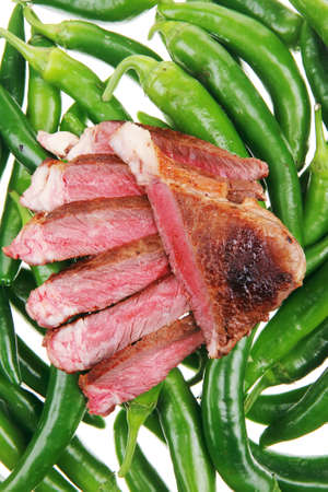 meaty food : roasted red meat steak sliced on a green hot chili peppers on a white back photo