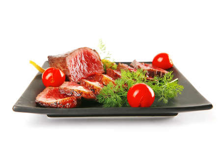 sliced meat on dark plate with vegetables photo