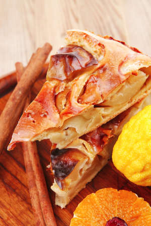 baked food: apple pie on wooden table served with lemon and cinnamon sticks photo