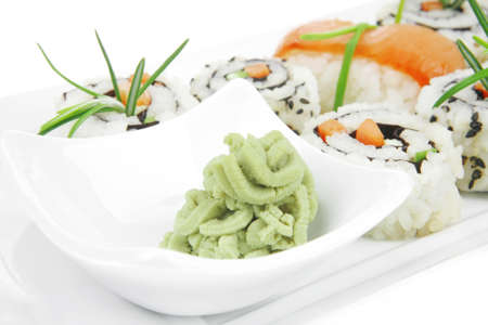 soysauce: Roll with Cucumber , Cream Cheese with raw Tuna and Salmon inside. on long white plate . Isolated over white background . Japanese traditional Cuisine